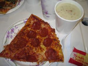 紙皿に大きめのピザの一片が乗っています。かなり大きいです。その上には厚手の紙コップにクラムチャウダーがたっぷり入っています。クラッカーもついています。。