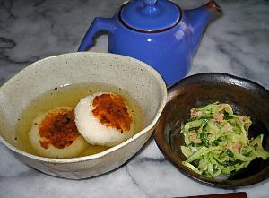 変形の深鉢に小さな焼きおにぎりがふたつ、たっぷりのお茶が注がれています。その右隣にはきゅうりとツナのサラダが。ブルーの急須がその向こうに見ています。