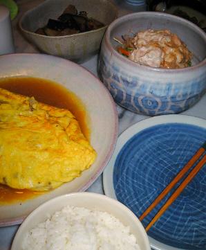 でっかいオムレツがインパクトがあります。サラダの入った鉢は、陶芸をやっていた時に作った自作の器。白っぽい地に抽象的な柄がブルーで描かれています。ナスの入った器やご飯茶碗なども見えます。