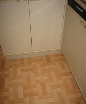 台所のコーナーらしき床の画像。木目の格子柄。タイルを貼ったにしては、つなぎ目も見えなくて綺麗に仕上がっています。