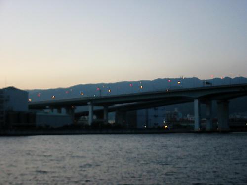 夕暮れ時の高速道路の風景。道路に灯りがともって、赤と黄色の蛍が飛んでいるようです。ゆったり流れる川と、赤く染まりかけてきた空の色が幻想的です。