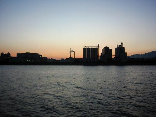 川を挟んだ対岸の様子。レンガ色に染まってきつつある空と、真っ黒に浮かび上がるビルや工場のシルエット、手前にゆるやかに流れる川面の黒ずんできた色合いが、空の夕焼けを一層際立たせて見せています。