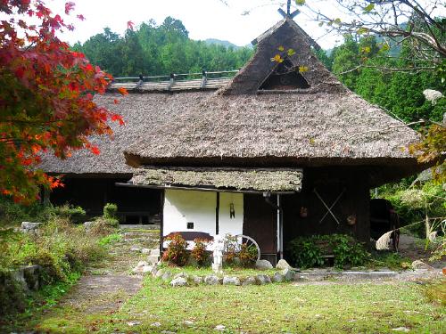 かやぶき屋根の古民家。庭の木が紅葉して、かやぶきの屋根の色に映えます。手入れがきちんとされているようで、小さな水車を模した車輪や、飾り付けが見えています。趣のある良い感じの家です。