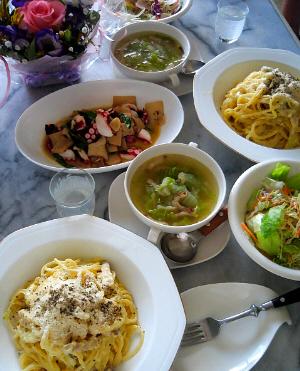 テーブルの上に、カルボナーラの盛り付けられた白いお皿、両手持ちの小さめのスープカップ、サラダの小鉢、前菜のタコとエリンギの炒め物、それぞれ白い器に入っています。二人分のお皿が並んでいる状態。ピンクのバラの周りに紫の花をアレンジしてある小さめのテーブルブーケ。透明の冷酒のグラスに白っぽい液体が入っています。
