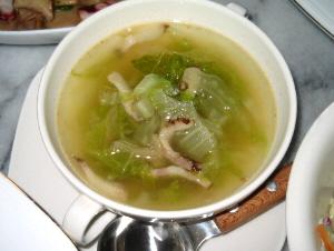 四角い受け皿に、丸い両手もちのスープカップ、小さなスープスプーンも添えられています。透明なスープに白菜と細切りにしたベーコンが浮かんでいます。
