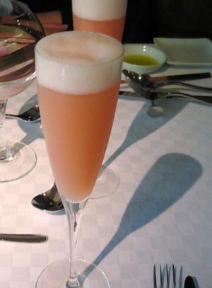 真っ白なテーブルクロスに淡いピンク液体が入ったシャンパングラスが2つ。グラスのシルエットがテーブルクロスに映って、影が斜め右に傾いでいます。