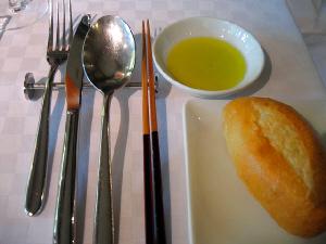 シルバーのカトラリー・レストに、細身のナイフ、フォーク、スプーン、そして箸が並べられていて、どの年代の方にもゆっくり食事して頂けるようにとの配慮が伺えます。白い角皿に焼きたてのパンがひとつ。丸い小皿に入っている黄色っぽい液体は、オリーブオイルです。