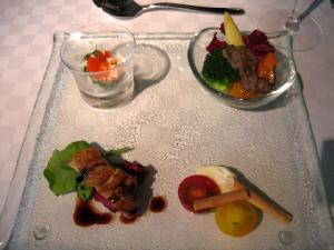 正方形の大きめのガラス製のお皿に、バランスよく並べられた4種類の前菜。楕円形の小さな小鉢に、温野菜、ブロッコリー・人参・ヤングコーンが見えています。お猪口のグラスには、エビのカクテル、とびっこ乗せ、地下置きに小さなトマト赤と黄色とモッツアレラチーズの盛り合わせ、そして皮をこんがり焼いたチキンには、黒いソースがかかっています。