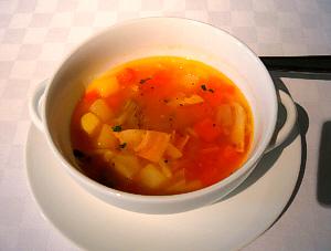 白い丸皿の上に乗った白い丸い両手持ちのスープカップ。赤いスープの色が映えて綺麗です。色々な野菜が見えています。