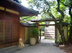 純和風な格子戸の玄関。入り口両脇に狛犬風なシーサーの置物が。