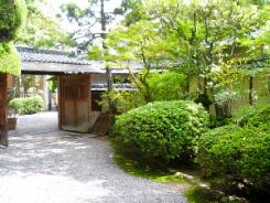 日本庭園風な入り口。入り口の屋根付きの門を入ると、玄関まで白い玉砂利が敷き詰められていて、植木の緑を一層引き立てています。