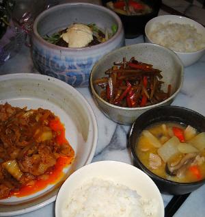 ご飯、具沢山の味噌汁、大きめのお皿に豚キムチ、変形のグレーの深鉢に、きんぴらごぼう、丸い大きめの陶器のボウルにサラダらしきものが入っているのが見えています。