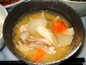 黒っぽい器にたっぷり野菜の味噌汁。人参の赤や、しめじ、大根の色合いが黒い器に映えますね。