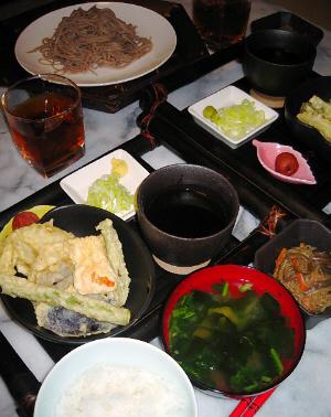 黒い竹細工のミニお盆?その上に天ぷらの入った黒い器、天ツユの入った、やはり黒っぽい器、四角い小さな皿にネギと生姜の薬味が。そして梅干がひとつ、小さな皿に乗せてあります。お盆の前にはご飯と味噌汁、そして煮物のようなものが入った小鉢が見えます。