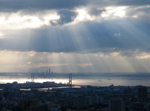 全体がグレーと沈んだブルーの風景。街並みの向こうに部分的に白く光る海が広がって、厚い雲の切れ間から太陽の光がうっすらと射しています。光のカーテンがオーロラのように出来て、色合いの無い世界が一層幻想的に見えています。