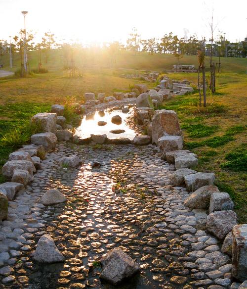 公園内に作られた人工の川の水辺。水が殆ど無く、少し残った水溜りに夕日が反射してまばゆく光っています。細い人工の川がまるで小道のように見えて、ずっと続く先は夕日の中に消えているように見えます。