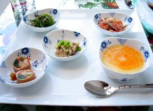 白い大きな角皿に、小鉢が5個乗っています。茎ワカメの煮たもの、鶏肉の山芋巻き、茶碗蒸し、おから、人参の炒め物がそれぞれ盛られています。