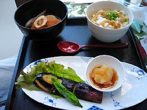 黒い塗りのお盆に、小さめの丼には豆腐と大根おろしの乗ったご飯、ミニおでんの入った黒い鉢、楕円形の平皿には、茄子の焼いたもの、小鉢に大根おろしも添えられています。