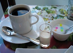 白い縦長の丸いコーヒーカップ。そして小さめの砂糖カップには、色とりどりの金平糖が入っていて、白さを一層際立たせています。