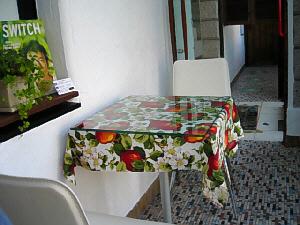 小さめの四角いテーブル、真っ赤なりんごや白い花の描かれた華やかなテーブルクロスがかかっています。床はタイルで、これならわんこが入っても衛生的ですね。