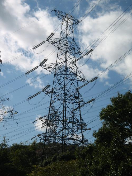 大きな送電線の鉄塔。木々の間が切れて鉄塔がどーんと大きく聳え立っている様子。真っ青な空、そして真っ白な雲を背景に、やたら存在感のある鉄塔です。