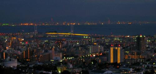 上の写真より少し濃い色になってきて、灯りが映える景色に。灯りがともる街並みと、ライトアップされた大きな橋、その向こうに広がる海、そして海の向こうには対岸の街の明かりが見えています。