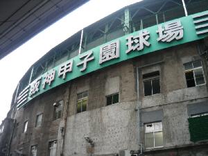 阪神甲子園球場と大きな看板が掲げられたドーム状の建物。外壁はかなり古いコンクリートで覆われています。