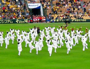 グリーンの芝に真っ白な衣装が映えています。両手を上に上げて音楽に合わせて躍っている様子。カメラマンの姿も見えます。