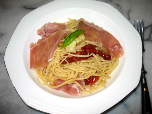 真ん中が窪んでいる白い八角形のお皿。パスタとドライトマトの赤、生ハムのピンク、トッピングに飾ったスイートバジルの緑が色鮮やかな一皿です。