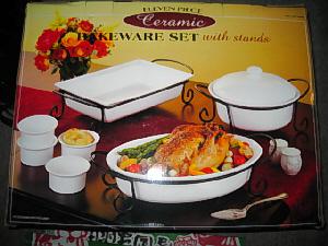 黒いスチールの足台の上に、白い大き目の角皿、楕円形の皿、ふたつきの丸ポットの3種類の容器、ソース入れに丸い筒型のカップが4つのセットです。