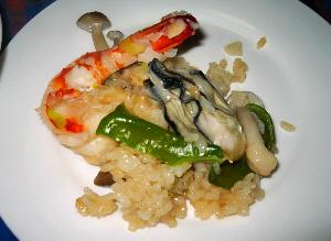 白い小皿に取り分けたパエリア。大きめのエビと牡蠣が美味しそうです。