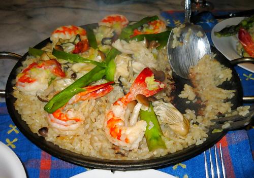 パエリア鍋いっぱいにご飯、エビ、牡蠣、アスパラ、しめじ等、たっぷりの具と取り分け用のスプーンですくったところは、おこげが見えています。