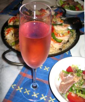 シャンパングラスに注がれたピンク色の液体。その隣にはサラダ、向こうにパエリア鍋が見えています。