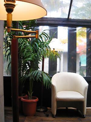 テラスの一角。白い椅子と椰子の木、手前にフロアスタンドの照明。窓はビニールのようなもので覆われ、屋根は透明の強化ビニール材のようなもので覆われています。格子にまっている窓の状態から、夏場は吹き抜けなんだろうと窺えます。