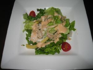 白い大き目の平角皿に盛られたサラダ。レタスにトマト、ヤングコーン、オリーブなどが入っています。
