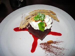 白い丸皿に赤いソースが×印状に、その上にチョコレートケーキ、たっぷりの生クリームが。やはりミントと飴の飾りつき。