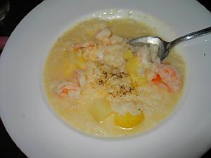 丸い白い大き目の平皿に盛られたリゾットじゃが芋とエビがアクセントのリゾットです。
