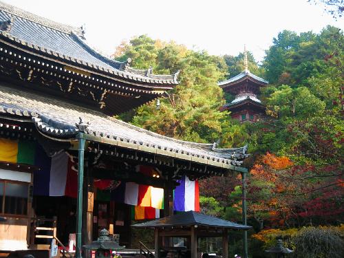 お寺の本堂の一部と、木々の間に見える塔。まだ残っている紅葉が綺麗です。本堂の軒下には名前は知りませんが色とりどりの布の幕が、白・赤・黄色・青・緑と鮮やかな色合いです。