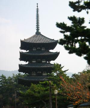 こちらはぐっと和風なたたずまいの五重塔。緑の木々の上に顔出した全体に黒っぽい色合いの建造物です。