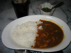 白いカレー皿に盛られたカレーライス。薬味らしきものと飲み物が入ったグラスも見えています。