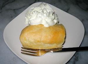 見た目は出来損ないのエクレアの半分のように見える白い角皿に乗ったデザート。生クリームがたっぷり添えられています。