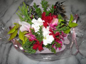 透明のビニールの両端をキャンディー包みのように絞ってリボンを結び、真ん中に水に強い紙を置いてオアシスを乗せ、花や葉を挿しただけの簡単フラワーアレンジメント。シクラメン等が入っています。