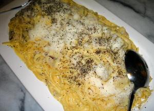 白い大きめの長方形のお皿一杯に盛られたカルボナーラ。上にかかったマルミジャーノレッジャーノが雪のように見えます。綺麗なクリーム色のパスタがチーズたっぷりなことを窺わせています。
