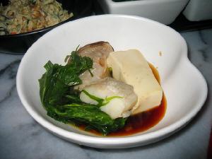 白いやや大きめの器に豆腐やタラ水菜の煮えたものが入っていて、ポン酢がかけられています。