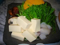 グレーの四角い大きめの平皿に、豆腐や野菜タラなどが盛り付けられています。黄色く見えているのは銀杏の葉のようです。