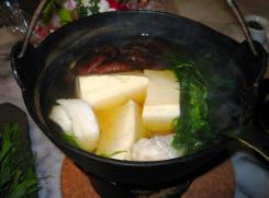 鉄鍋のアップ画像。豆腐、しいたけ、タラ、水菜が煮えて入っています。湯気が立って熱そうです。