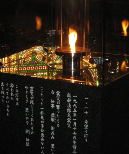 黒い石柱の上にガラスケースに入れられたランプが、ゆらゆらとゆらめく炎を上げています。炎の色合いとゆらめきが、ルミナリエの電飾の色とは対照的に質素で静かで、逆により一層幻想的に思えます。