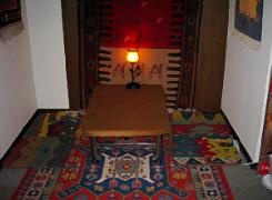ペルシャ絨毯がタペストリーとしてかけられ、テーブルの下にも絨毯が、四角い座布団上のものも、同じくペルシャ絨毯のようです。華やかな色使いが異国情緒満点。地下に座る形は日本人には馴染み深いですね。