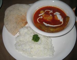 白い丸皿に乗っているのは、ハーブを練りこんだピタパン、丸い白いボウルに赤いスープ、中に皮の剥いた大きめの茄子が見えます。そして普通の白いご飯も添えられています。