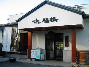 浜福鶴と店の入り口上部の屋根の形をした白地の軒に立体も字が貼り付けられています。お店の前には酒蔵らしく大きな樽が置かれています。